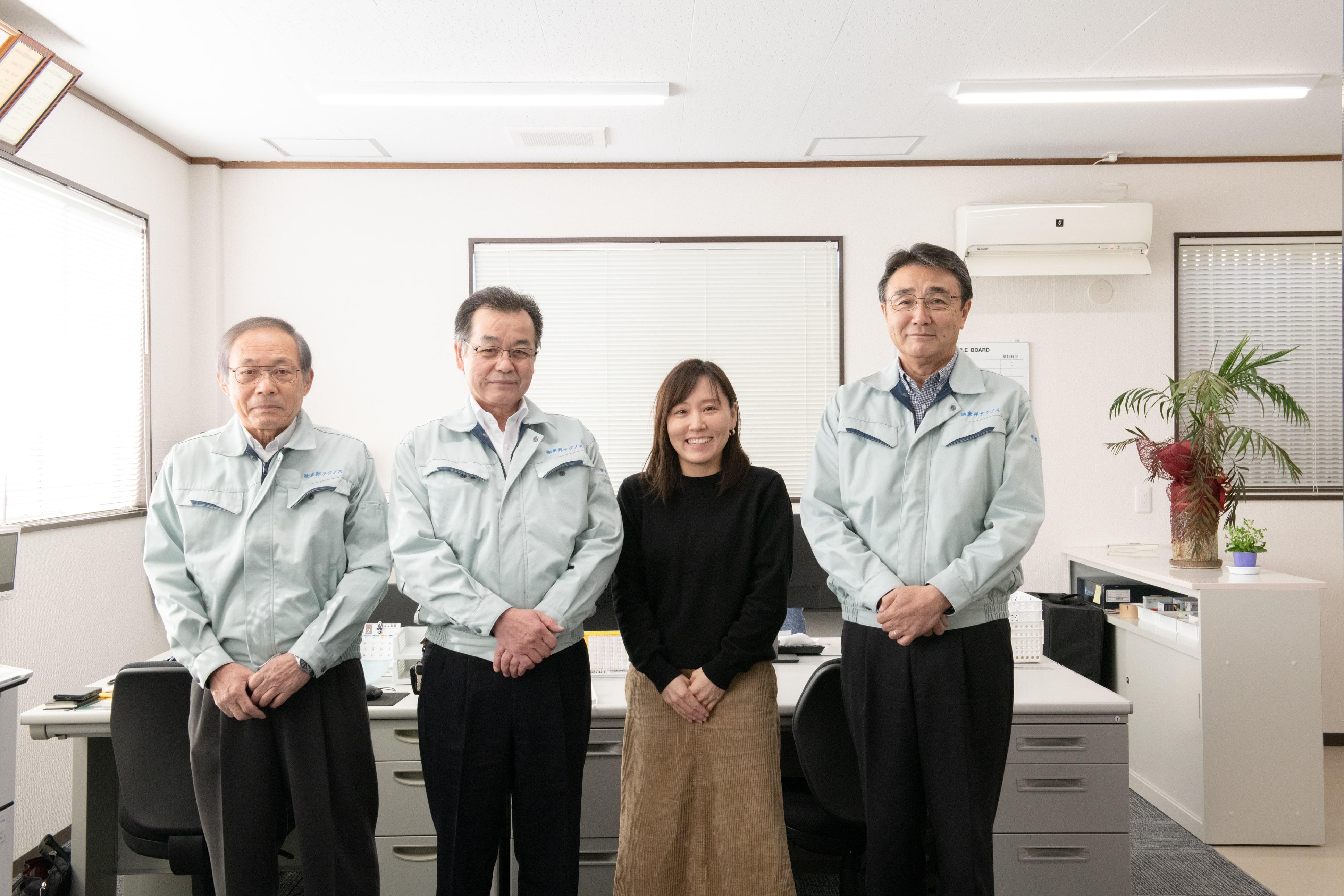 新入社員が、東邦テクノスの代表望月英男、役員と一緒に並んで事務所で立っている写真